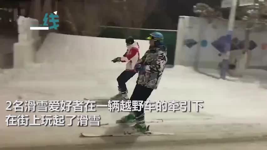 视频-张家口降下中雪 两男子越野车牵引街头滑雪自