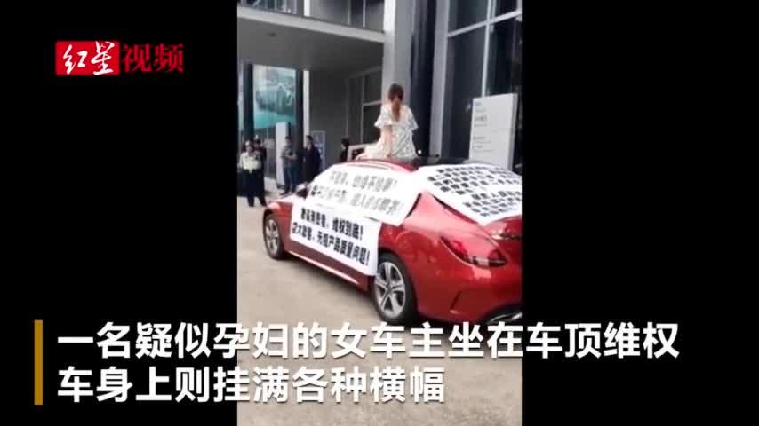 视频:广东疑有孕妇坐奔驰车顶维权 现场有人打伞保