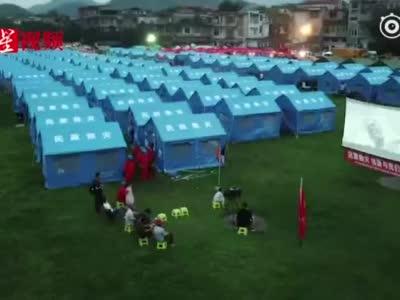 四川长宁地震6.0级 安置点放起了坝坝电影 群众打伞观看
