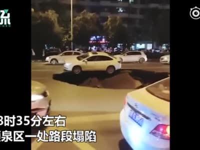 安徽阜阳路面突现大坑 一辆轿车悬在坑边