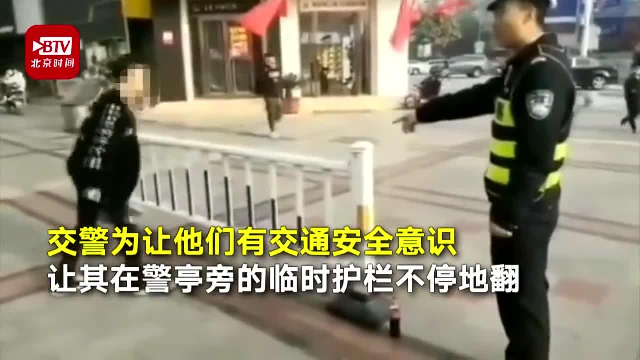 """视频:俩小伙翻护栏被抓现行 交警罚其翻护栏""""让你"""