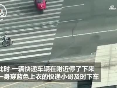 男子坐轮椅在斑马线上徘徊,快递小哥赶忙下车,避过车流将其送到马路对面